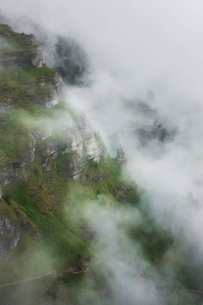 Gorgeous view of mountain side engulfed in fog stock photo
