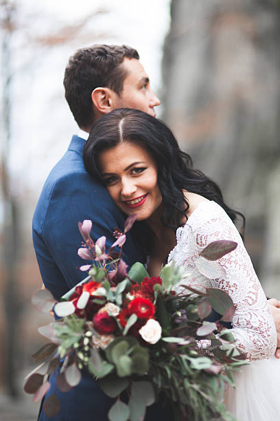 Gorgeous wedding couple kissing and hugging in forest with big stock photo