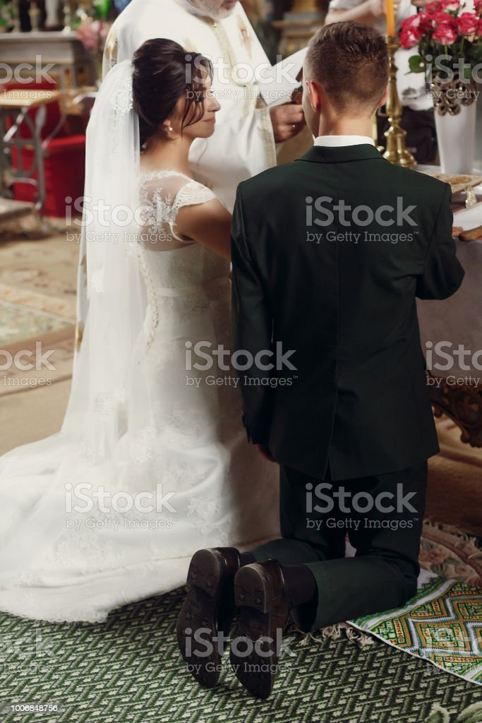 gorgeous wedding couple standing at altar making vows at official ceremony in old church. traditional moment of marriage of bride and stylish groom stock photo