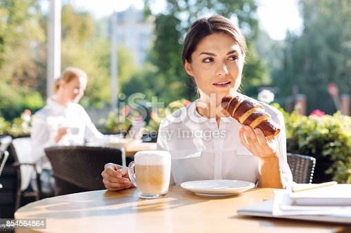 istock Gorgeous woman eating croissant in a cafe 854564864