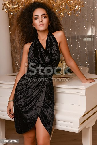 young slim seductive woman with dark curly hair wearing black velvet dress near white piano
