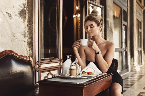 Gorgeous woman is wearing black dress in a vintage Italian cafe