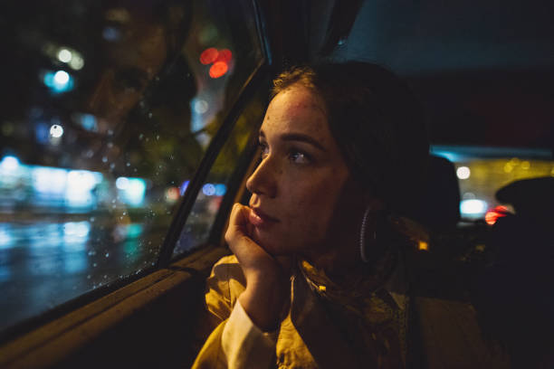 Gorgeous woman looking through the car window during her taxi ride stock photo