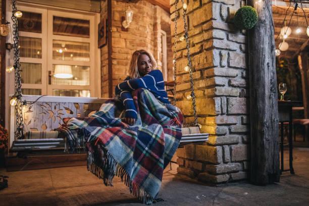 wunderschöne frau auf einer gemütlichen veranda-schaukel - veranda decke stock-fotos und bilder