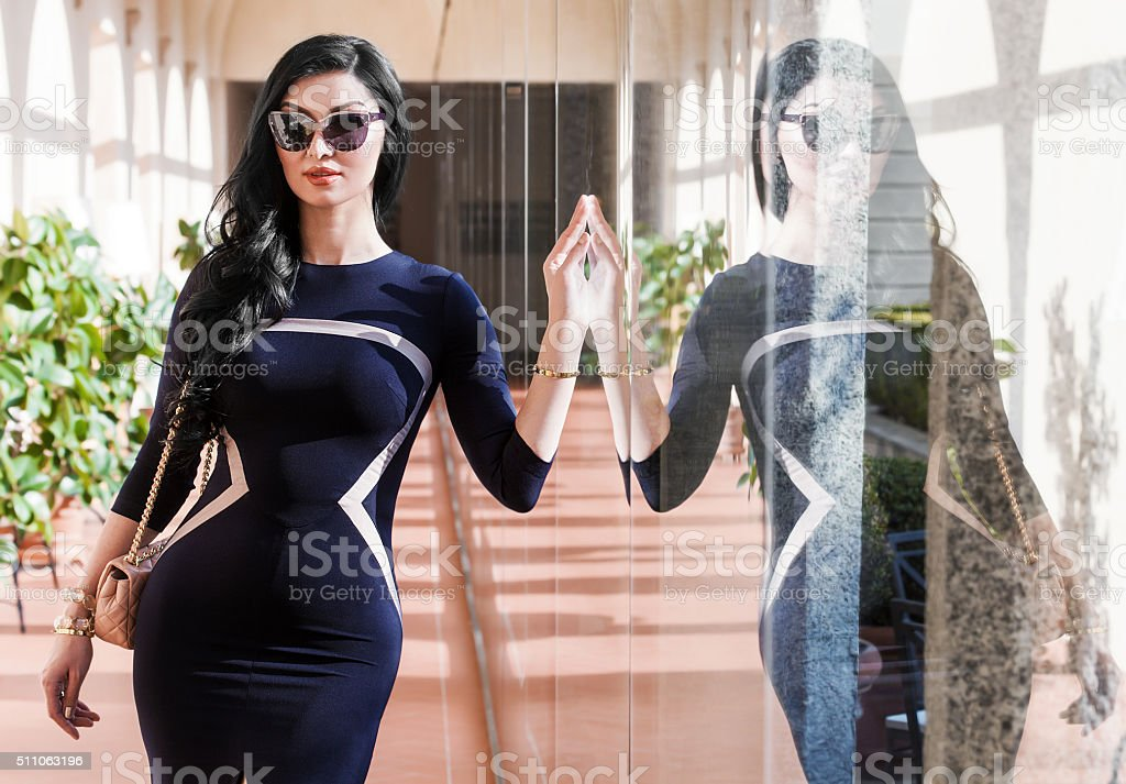 Gorgeous woman portrait wearing blue dress and sunglasses with r stock photo