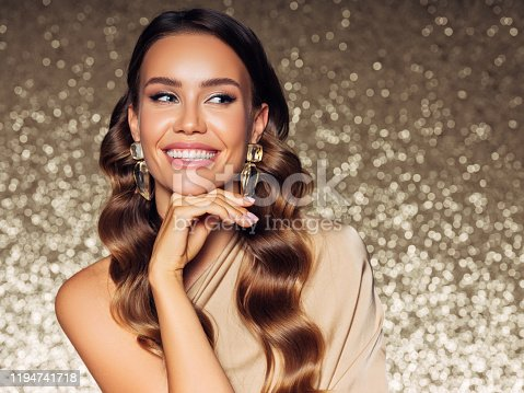Gorgeous woman posing in front of golden background
