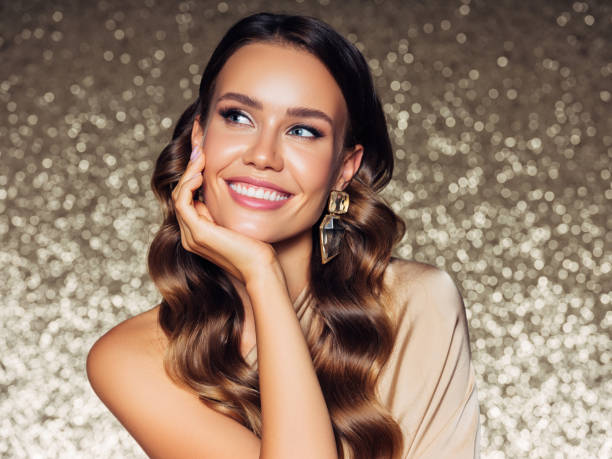 gorgeous woman posing in front of golden background - makeup foto e immagini stock