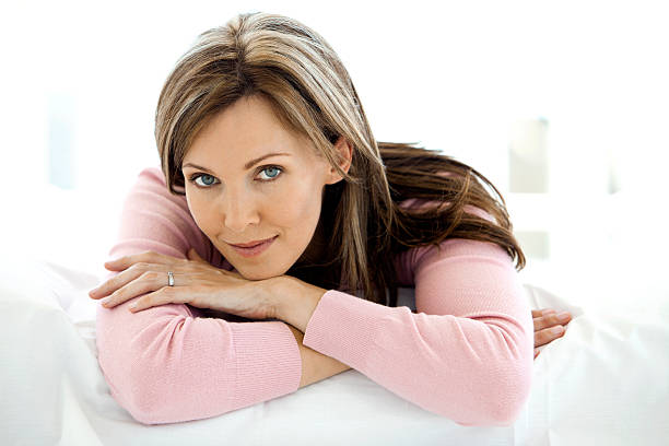Gorgeous woman relaxing on bed stock photo