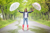 istock Gorgeous woman stands on a rainy asphalt road in the nature holding two umbrellas with arms wide open. 1240302914