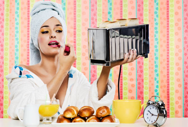 Gorgeous woman's, breakfast lipstick and toaster. One beautiful woman having breakfast, she is using a shiny toaster as a mirror and putting some lipstick on. She is wearing a bathrobe and has her hair wrapped in a towel. Colorful background and horizontal format. Concept young adult lifestyle and body care. diva human role stock pictures, royalty-free photos & images