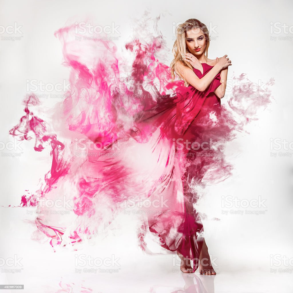 Gorgeous young adult blonde in pink dress with smoke stock photo