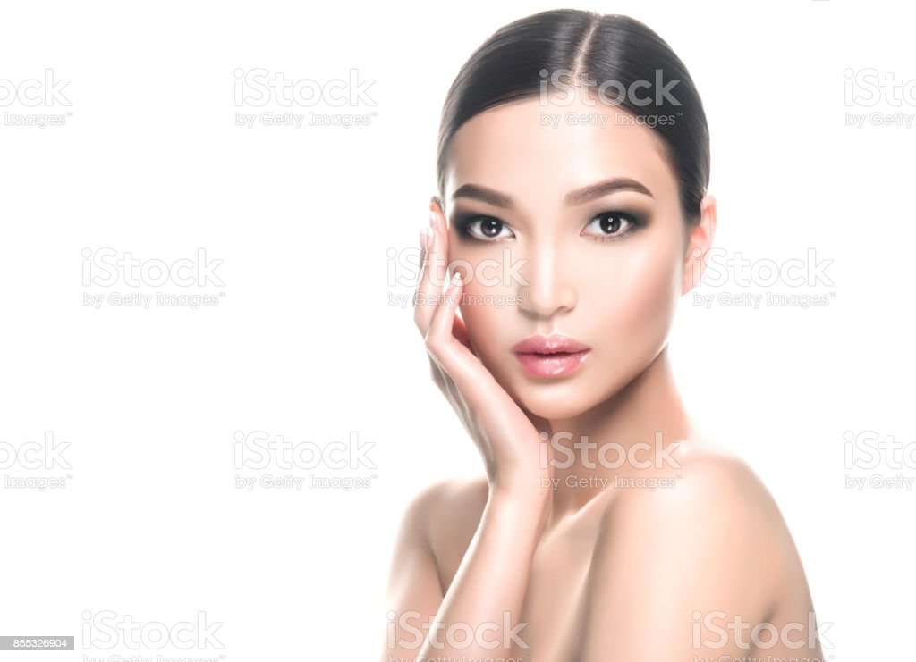 Gorgeous, young asian woman with clean, fresh skin is touching own face. Cosmetology. stock photo