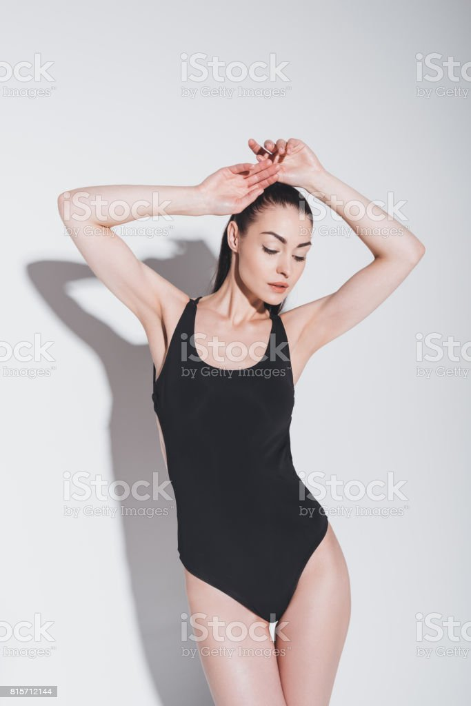Gorgeous young brunette woman in stylish bodysuit posing with raised hands on grey stock photo