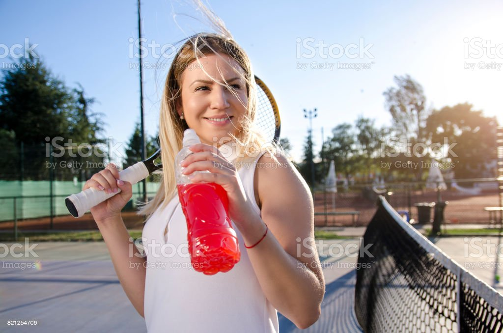 Gorgeous young female tennis player drinking energy drink stock photo