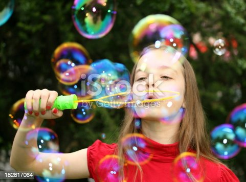 Gorgeous young girl blowing huge soap bubbles outdoors.