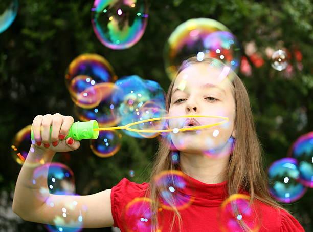 schöne junge mädchen blowing soap bubbles. - riesen seifenblasen zauberstäbe stock-fotos und bilder
