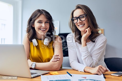 1031394390 istock photo Gorgeous young office workers sitting together at one desk staring at camera smiling while working in the office 1031397358