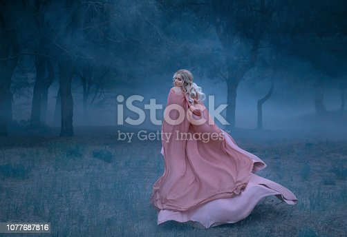 Gorgeous young queen with blond hair runs in a dark and dense scary forest full of white mist, dressed in a long, flying and flowing peach dress, a photograph of a beautiful woman in the moonlight.