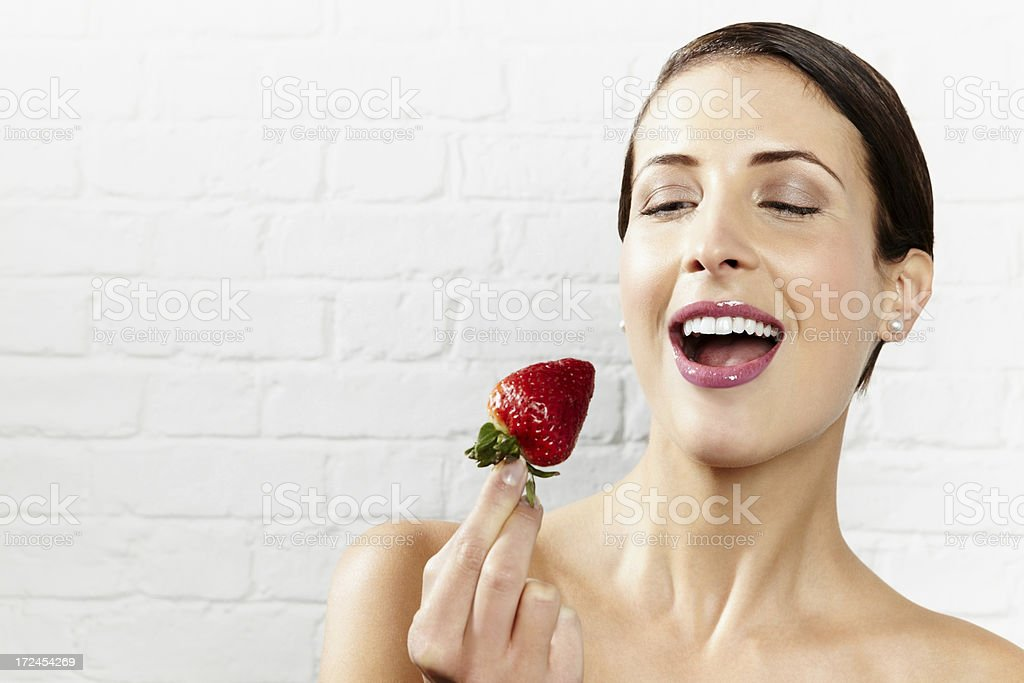 Gorgeous young woman about to eat a strawberry royalty-free stock photo