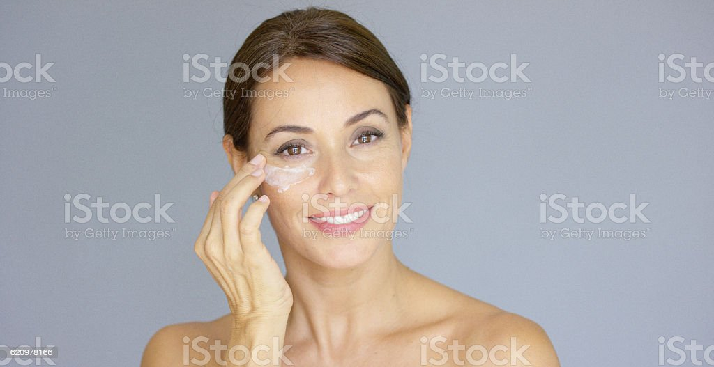 Gorgeous young woman applying face cream stock photo