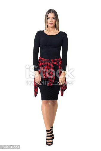 Gorgeous young woman in black dress walking and looking at camera. Full body length isolated over white studio background.