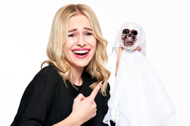 wunderschöne junge frau in hexenkostüm halloween skelett dekoration lachend und mit einem finger auf sie halten. halloween-konzept auf weißem hintergrund. - zum totlachen stock-fotos und bilder