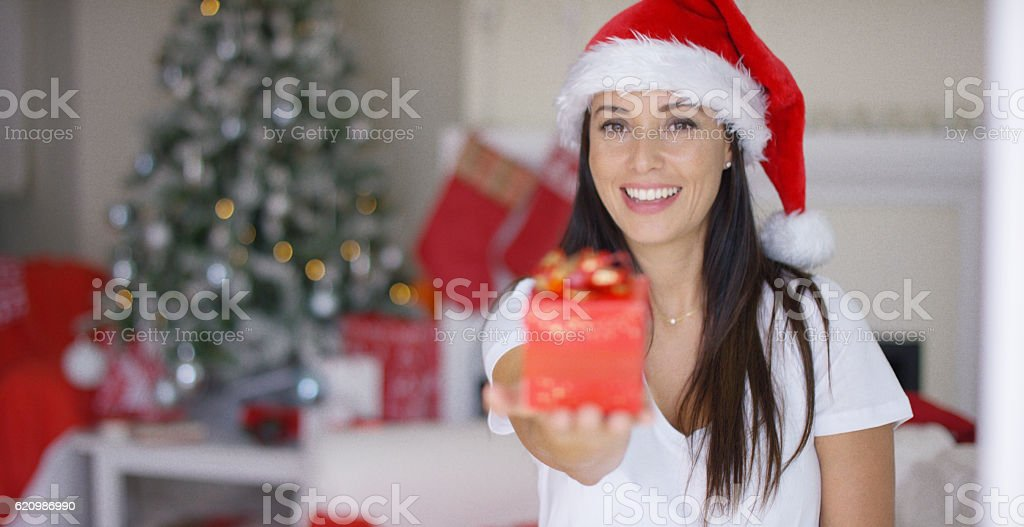 Gorgeous young woman offering an Xmas gift foto royalty-free