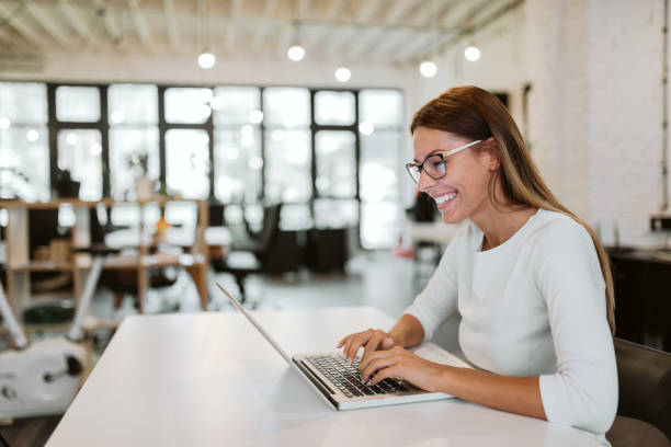 Gorgeous young woman using laptop in bright office. Close-up. Gorgeous young woman using laptop in bright office. Close-up. coworking stock pictures, royalty-free photos & images