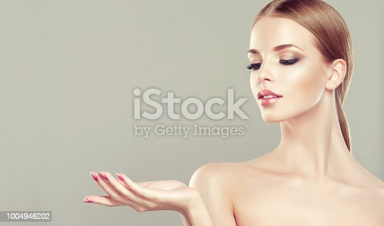 1070715740 istock photo Gorgeous, young woman with clean, fresh skin is holding graceful hand in front ownself. Beauty and cosmetology. 1004946202