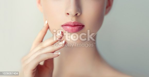 1070715740 istock photo Gorgeous, young woman with clean, fresh skin is holding graceful hand in front ownself. Beauty and cosmetology. 1026057404