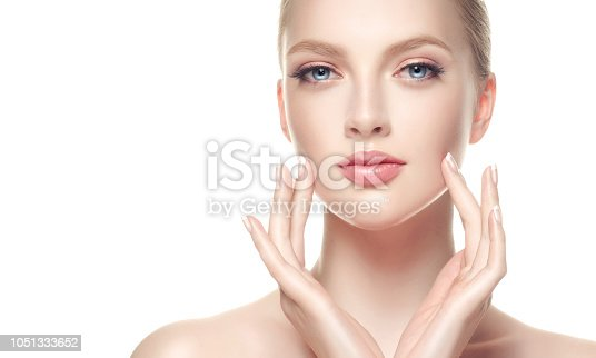 1070715740 istock photo Gorgeous, young woman with clean, fresh skin is holding graceful hand in front ownself. Beauty and cosmetology. 1051333652