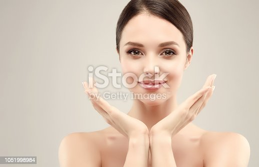 1070715740 istock photo Gorgeous, young woman with clean, fresh skin is holding graceful hand in front ownself. Beauty and cosmetology. 1051998984
