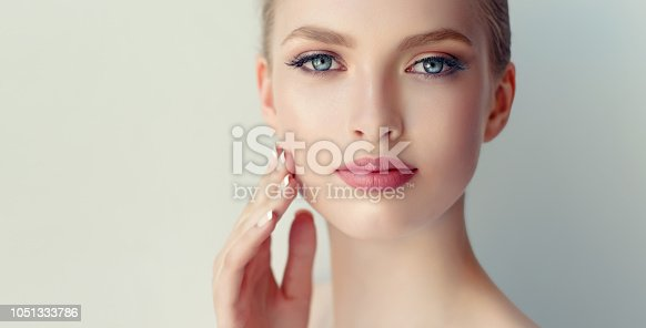 1070715740 istock photo Gorgeous, young woman with clean, fresh skin is touching own face.  Light smile on the perfect face. Cosmetology. 1051333786