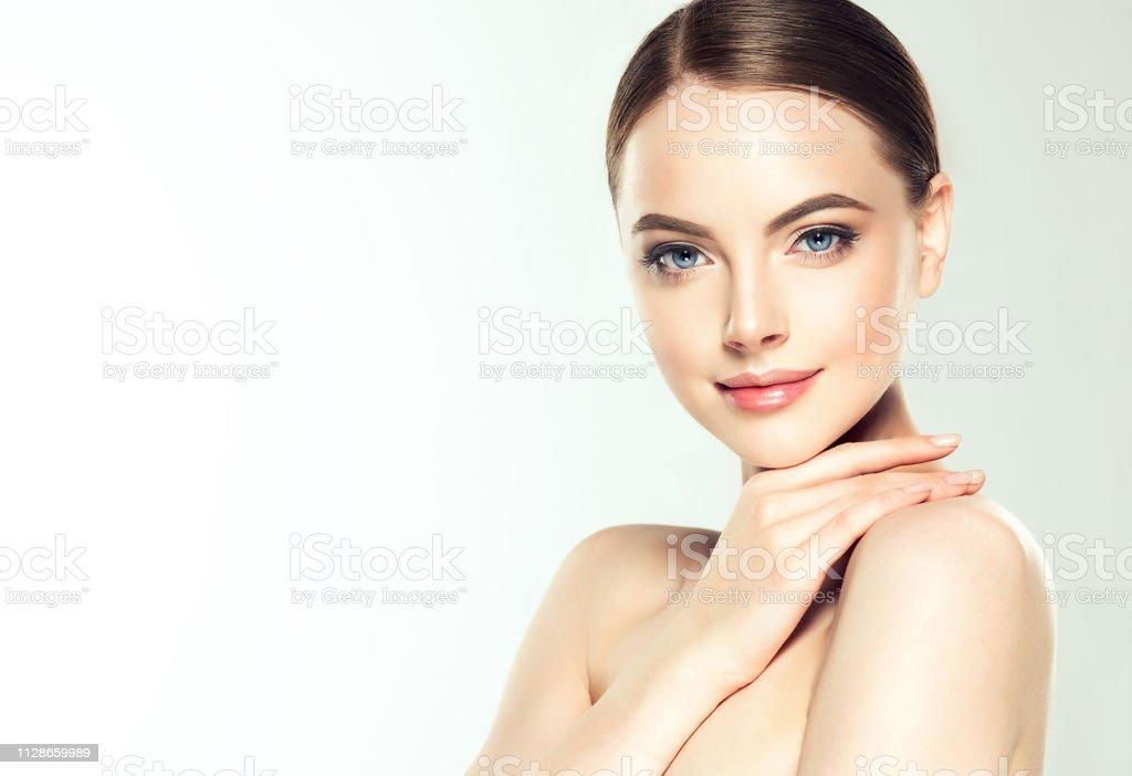 Gorgeous, unga kvinnan med ren, fräsch hud är rörande eget ansikte.  Ljus leende på det perfekta ansiktet. Kosmetologi. - Royaltyfri Alternativ terapi Bildbanksbilder