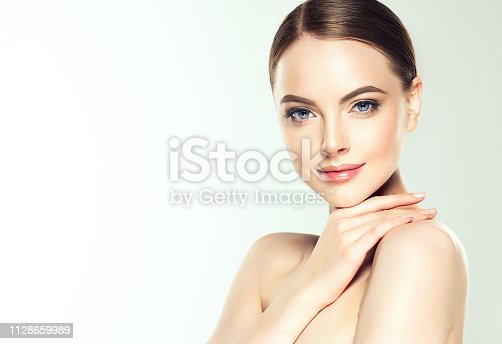 Gorgeous, young, brown haired woman with clean fresh skin and delicate make up is touching the face.  Light, tender smile on her lips and soft gesture of hand. Facial treatment, cosmetology, beauty technologies and spa.