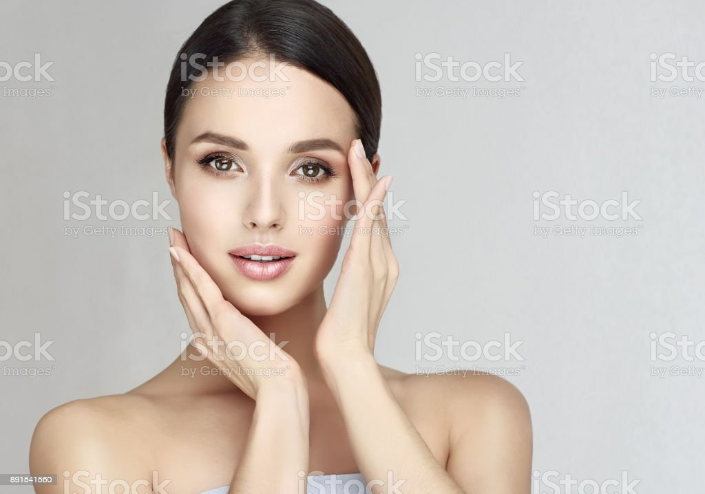 Gorgeous, young woman with clean, fresh skin is touching own face.  Light smile on the perfect face. Cosmetology. royalty-free stock photo