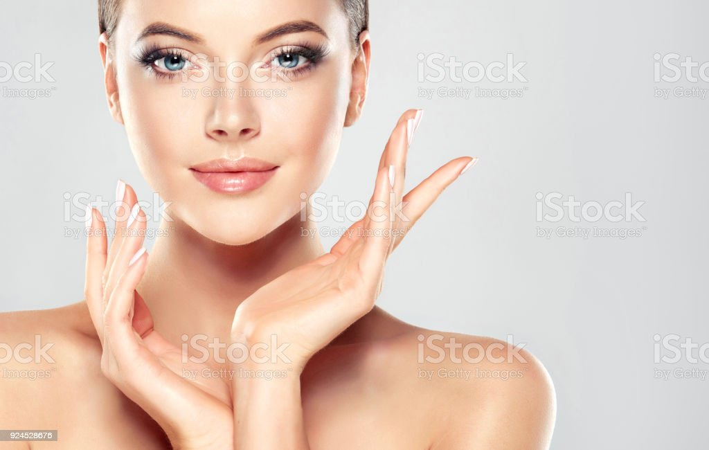 Gorgeous, young woman with clean, fresh skin is touching own face.  Light smile on the perfect face. Cosmetology. stock photo