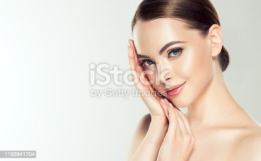 Gorgeous, young, brown haired woman with clean fresh skin and hair gathered in neat  hairstyle is touching the face. Soft make up and light smile on the perfect face.  Facial treatment, cosmetology, beauty technologies and spa.