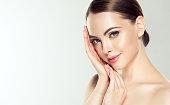 きれいで、新鮮な肌を持つゴージャスな、若い女性は、自分の顔に触れています。顔面治療.