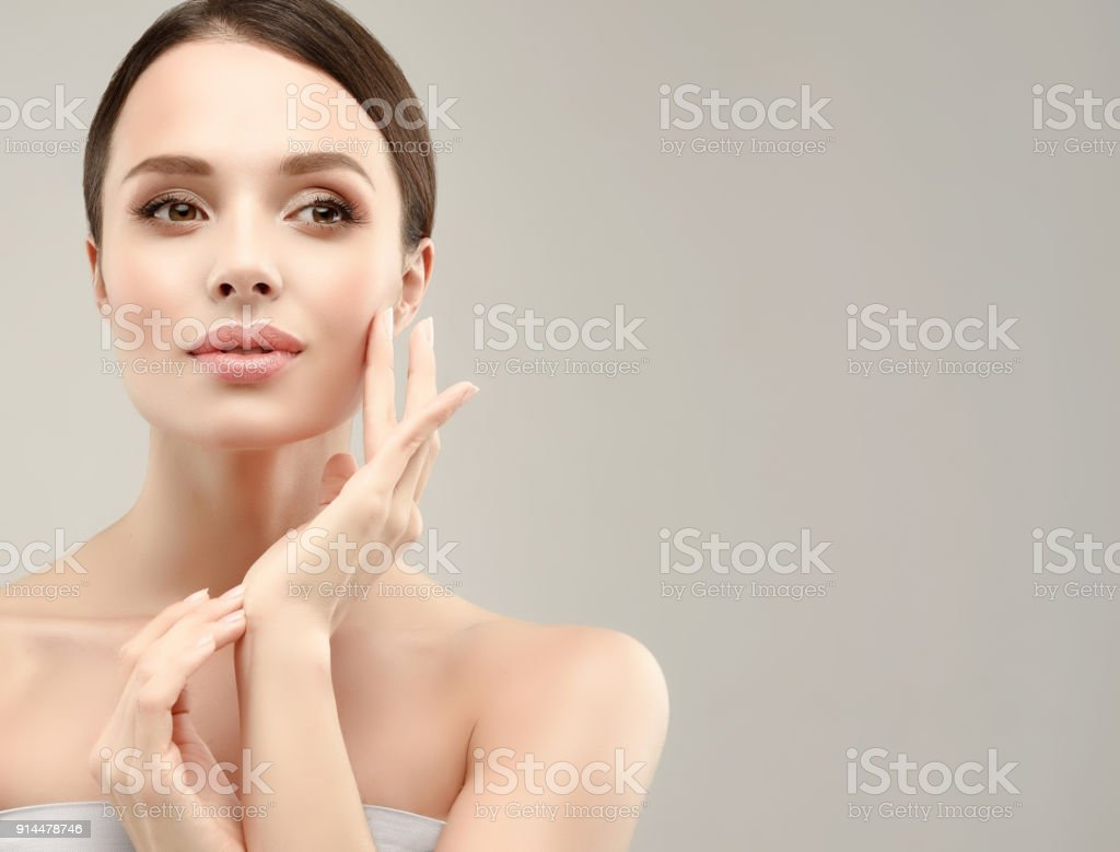 Gorgeous, young woman with clean, fresh skin is touching own face. Cosmetology. royalty-free stock photo