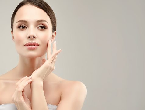 Gorgeous Young Woman With Clean Fresh Skin Is Touching Own Face Cosmetology - Fotografie stock e altre immagini di Accudire