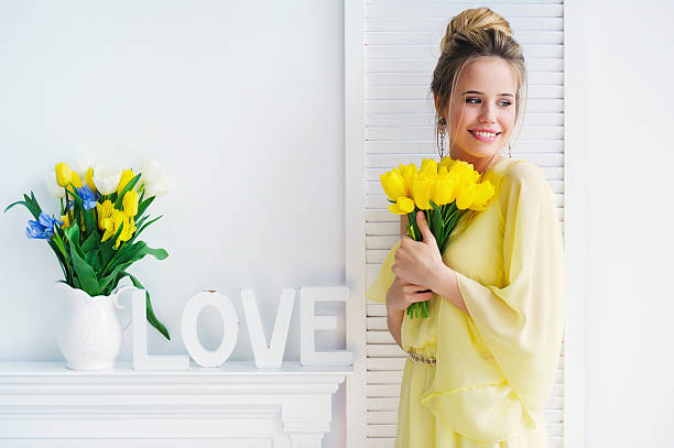 Gorgeous young woman with yellow tulips stock photo