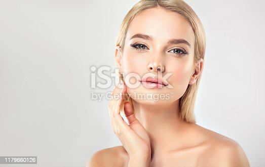 Gorgeous, young,woman with almond like eyes and fashionable hairstyle on the short blonde hair is touching tenderly the face. Facial treatment, cosmetology, beauty technologies and spa.