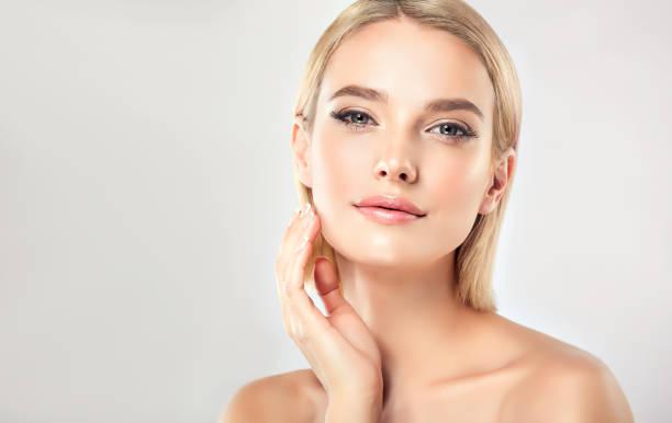 wunderschön, jung, frau mit mandel-ähnlichen augen berührt zärtlich das gesicht. gesichtsbehandlung, kosmetologie und spa. - beauty stock-fotos und bilder