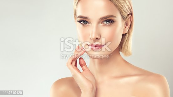 Gorgeous, young,woman with with almond like eyes and fashionable hairstyle on the short blonde hair is touching tenderly the face. Facial treatment, cosmetology, beauty technologies and spa.
