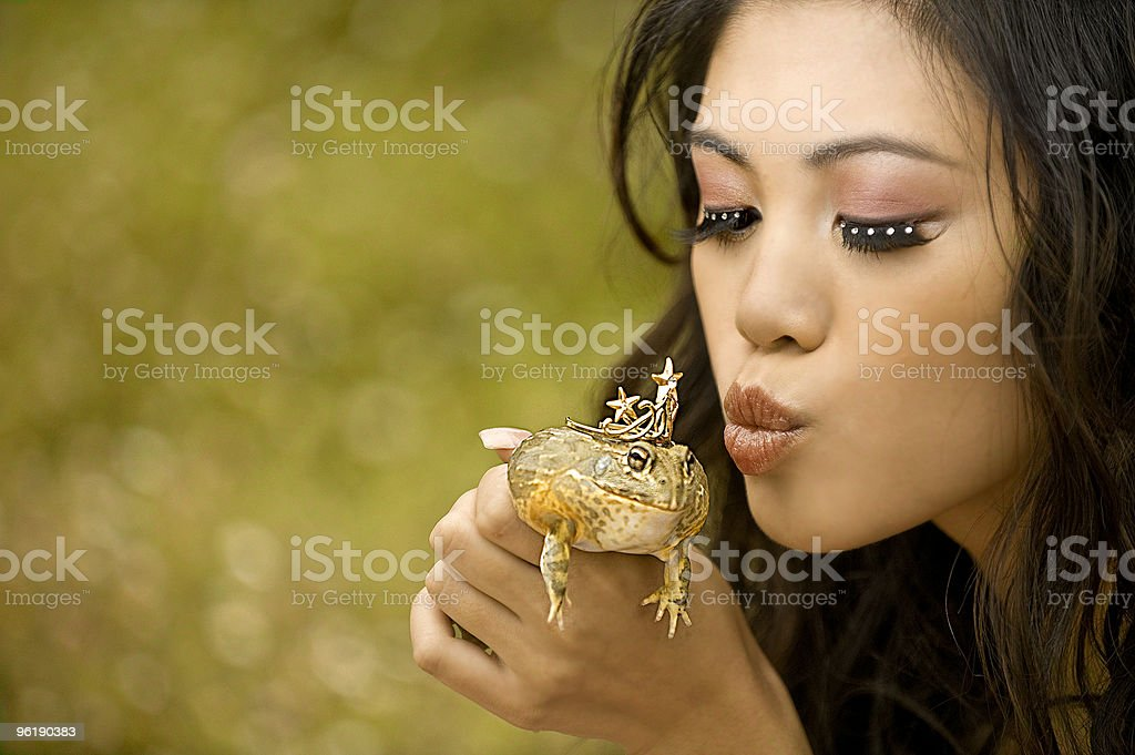 Gorgeously made up Princess holds Frog up for a kiss stock photo
