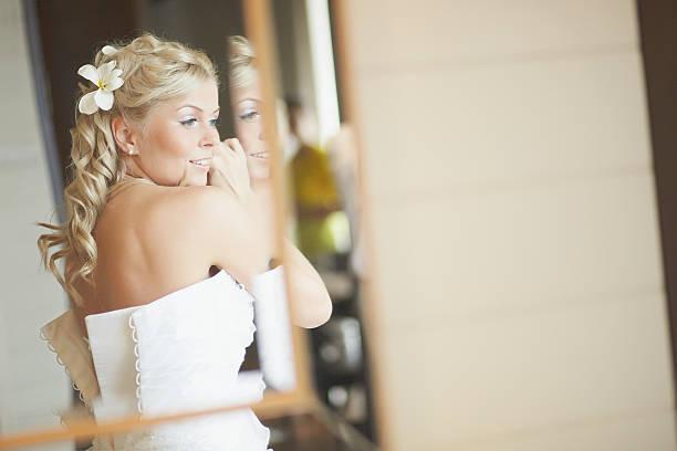 gorgerous brautpaar stehend vor spiegel, instandsetzung haar - hochzeits make up blaue augen stock-fotos und bilder