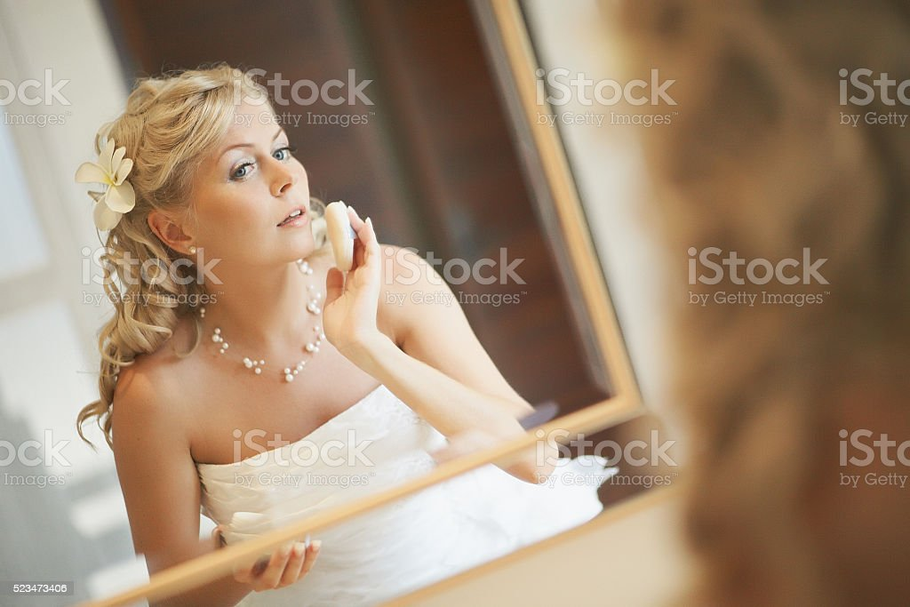 Gorgerous bride standing in front of mirror, fixing make up. stock photo