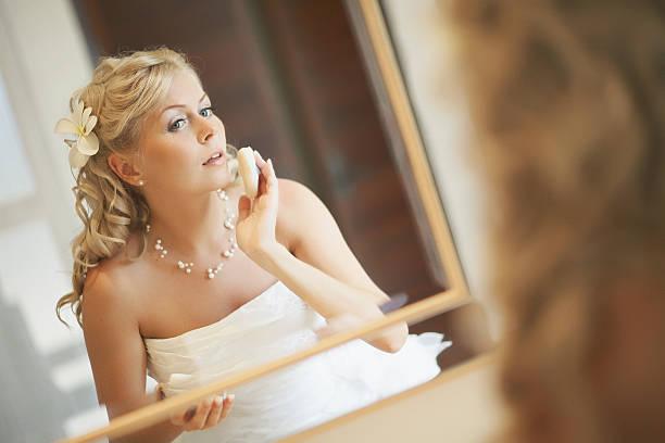 gorgerous brautpaar stehend vor spiegel, reparatur von make-up. - hochzeits make up blaue augen stock-fotos und bilder