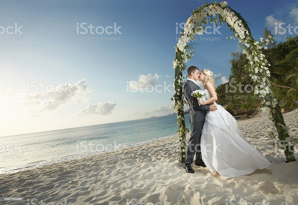Gorgerous couple kissing, standing under arch during sunset. stock photo